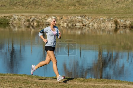 Photo for Running woman outdoor sport by river bank sunny day - Royalty Free Image