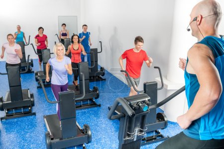 Photo for Alpinning class of young adults with fitness personal trainer - Royalty Free Image