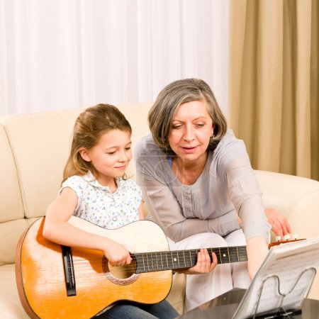 Young girl sing play guitar to grandmother