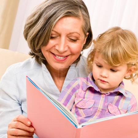 Grandmother and granddaughter read book together