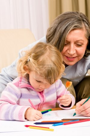 Cute little girl drawing with grandmother at home
