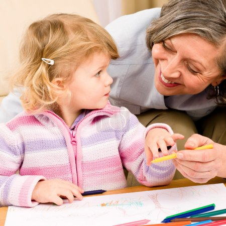 Little girl with grandmother drawing together