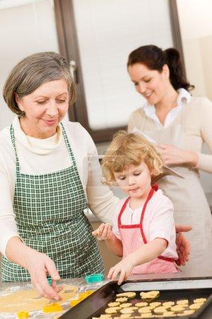 Photo pour Petite fille avec grand-mère, préparez des biscuits sur plateau - image libre de droit