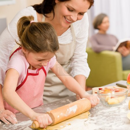 Photo for Mother and daughter making apple pie together grandmother check recipe - Royalty Free Image