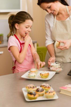 Little girl taste sprinkles decorating cupcake