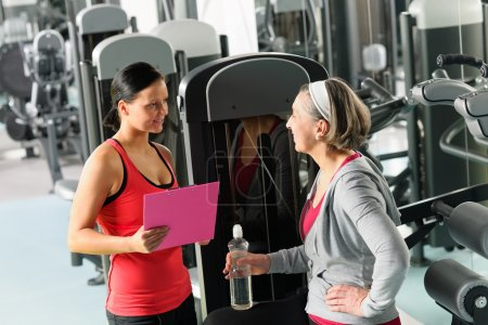 Photo for Senior woman with trainer discuss personal plan at gym - Royalty Free Image