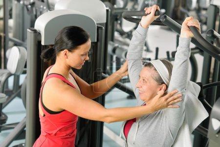 Photo pour Exercice femme senior sur presse épaule avec entraîneur personnel - image libre de droit