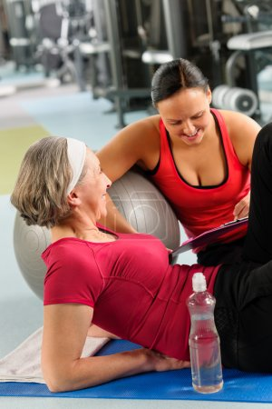 Senior woman on mat with personal trainer