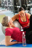 femme Senior sur tapis avec entraîneur personnel