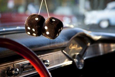 Photo pour Dés flous suspendus au miroir d'une voiture américaine vintage . - image libre de droit