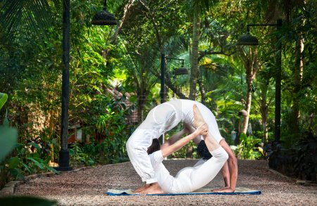 Photo for Couple Yoga of man doing chakrasana and woman doing dhanurasana poses in white cloth in the garden. Represents yin and yang - Royalty Free Image