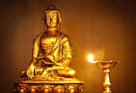 Golden Buddha with oil lamp