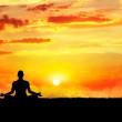 Yoga meditation in lotus pose by man silhouette at...