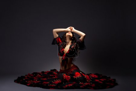 Photo for Young cute woman sit in gypsy black and red - dramatic posing - Royalty Free Image