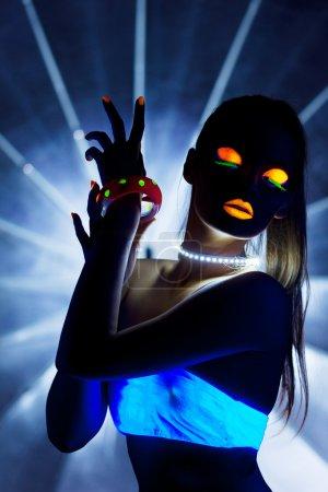 Photo pour Jeune fille à la danse disco maquillage ultraviolet dans noir - image libre de droit