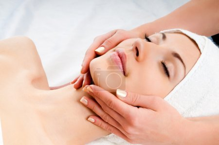 Photo for Beautiful young woman receiving facial massage with closed eyes in a spa center - Royalty Free Image