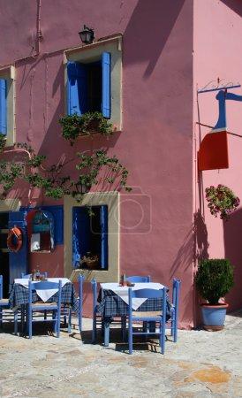 Photo pour Restaurant de taverne grecque avec chaises et tables bleues traditionnelles - image libre de droit