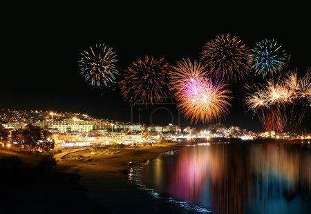 Photo pour Eau qui reflète les feux d'artifice de nuit dans la localité de vacances bord de mer, festive - image libre de droit