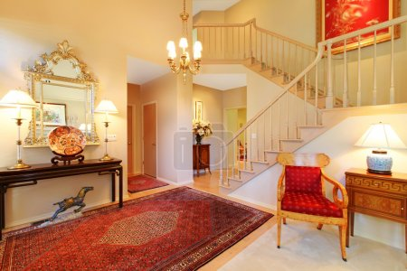 Luxury entrance living room with red rug, staircase.