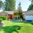 Cute small brown rambler house with red door and w...