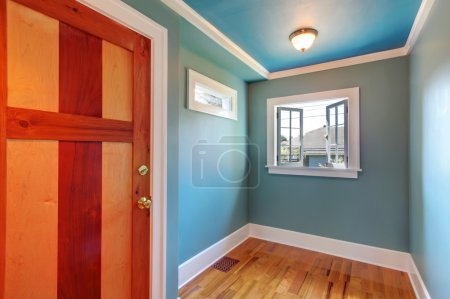 Cutom wood door in blue empty room with open window.