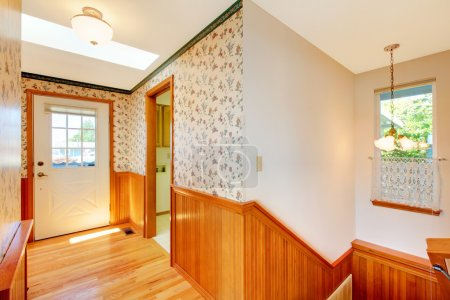 Sunny cozy hallway with staircase and front door and warm wood.