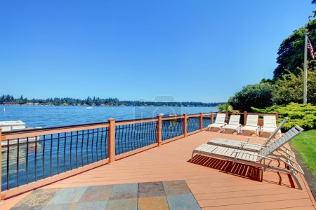 Lake waterfront deck with beach laying down chairs