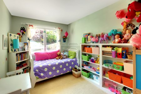Photo for Kids bedroom with green walls and purple bed and may toys. - Royalty Free Image