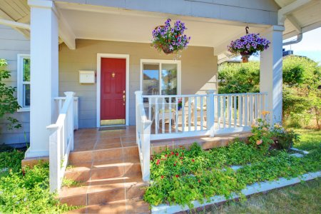 Photo pour Porche de la maison grise avec porte rouge et grilles blanches. - image libre de droit