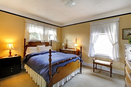 Photo pour Petite chambre confortable jaune avec couverture bleue et design élégant . - image libre de droit