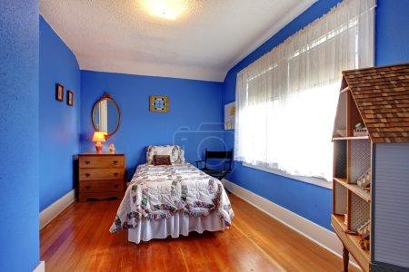 Photo pour Chambre d'enfants bleu vif dans le vieux style anglais avec plancher de cerisier et maison de poupée . - image libre de droit