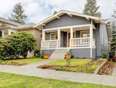Photo for Blue grey smal craftsman style house with white porch. - Royalty Free Image