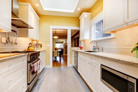 Yellow and white simple kitchen with skylight.