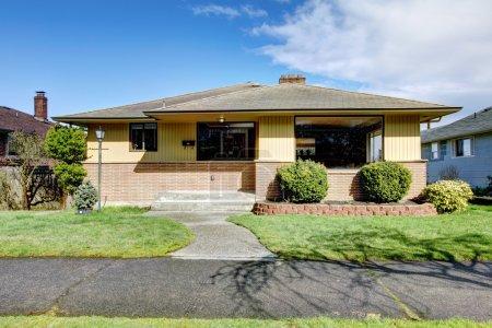 Small American yellow brick rambler house exterior...