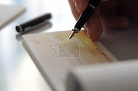 Photo pour Homme d'affaires qui fait le chèque - image libre de droit