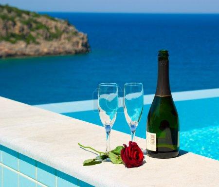 Photo pour Pique-nique romantique près de la piscine à débordement dans station balnéaire méditerranéenne de luxe. Champagne et rose. Grèce - image libre de droit