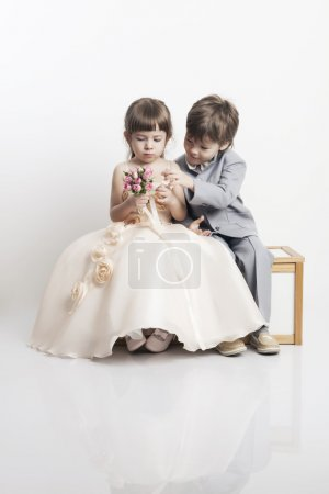 Portrait of two beautiful little boys and girls in wedding dresses