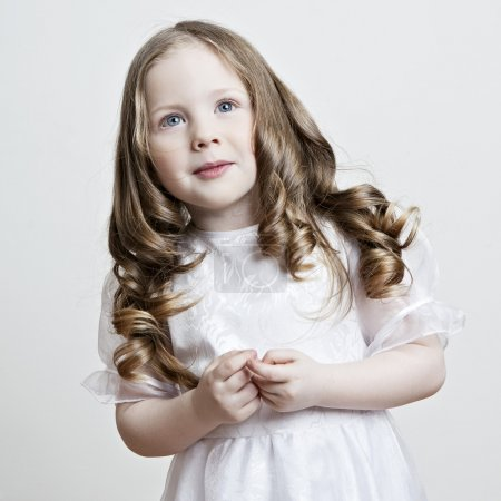 Portrait of a beautiful little girl in a white dress and veil on a white background
