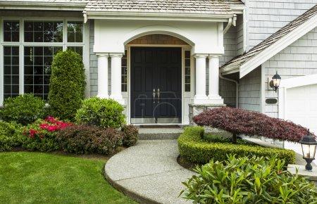 Photo pour Porte d'entrée à la maison, entouré de plantes saisonnières et partie Cour et trottoir en avant-plan - image libre de droit