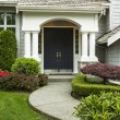 Front Door to home surrounded by seasonal plants a...