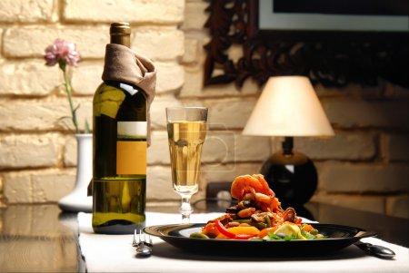 Photo pour L'intérieur du restaurant avec des tables servies, salade un verre de vin blanc - image libre de droit
