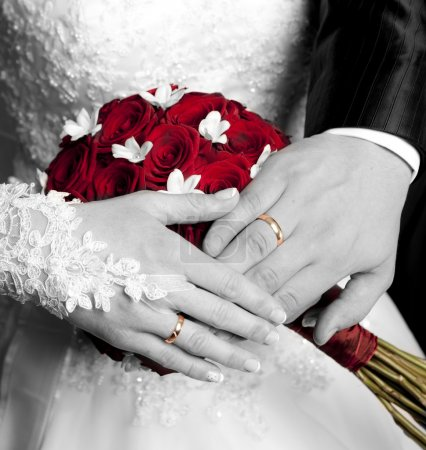 The hands of just married couple on the flowers background
