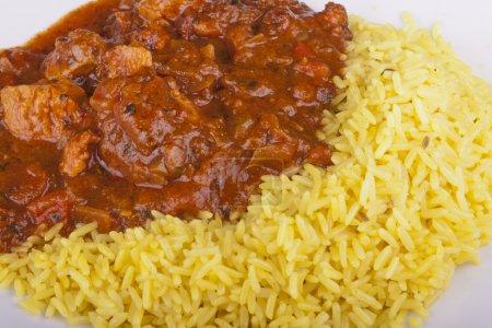 Foto de Foto de jalfrezi pollo con arroz pilau en un plato - Imagen libre de derechos
