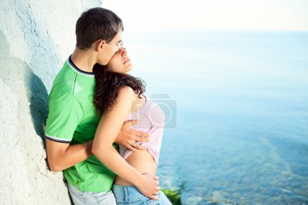 Photo for Young coupe hugging on the seaside near rock, sunny morning - Royalty Free Image