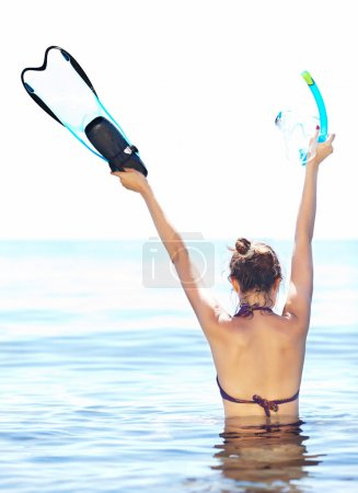 Photo for Young tanned woman holding flipper, mask and snorkel waist-deep in water, rear view - Royalty Free Image