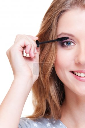 Close up portrait of smiley woman doing make up