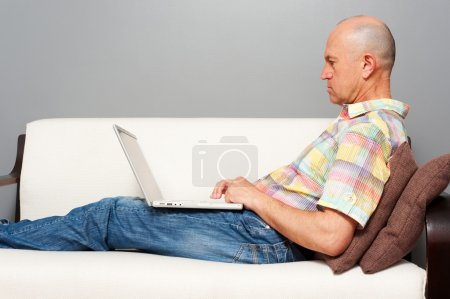 Man on the white sofa with notebook