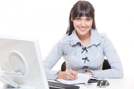 Smiley woman in office writing something in notebook