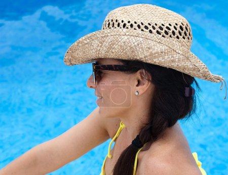 Photo pour Femme dans une piscine avec un chapeau de paille - image libre de droit