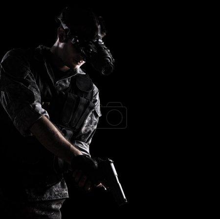 Photo pour Soldat portant un uniforme de camouflage urbain avec des lunettes de vision nocturne armées d'un pistolet sur fond noir - image libre de droit